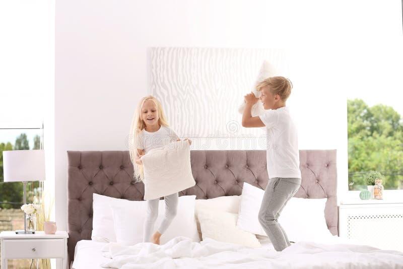 Bambini felici che hanno lotta di cuscino sul letto fotografia stock libera da diritti