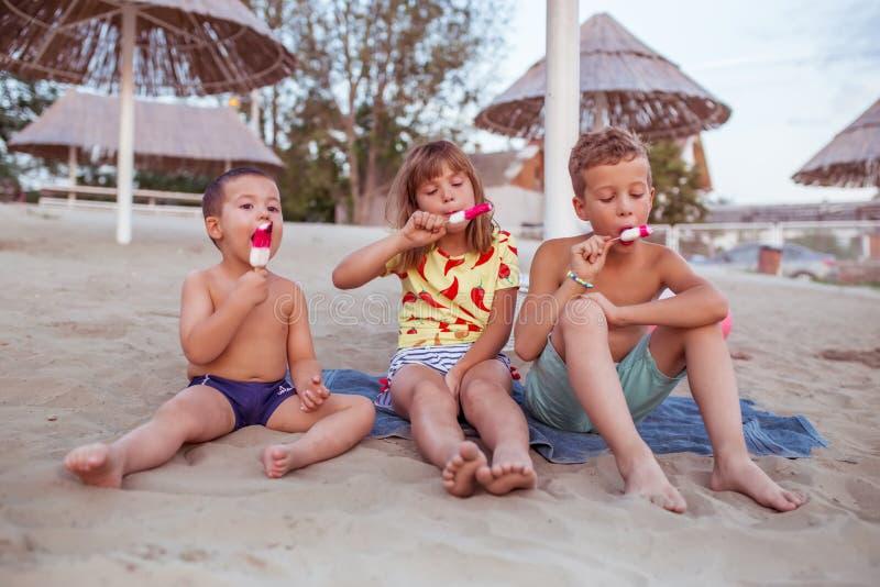 Bambini felici che mangiano il gelato sulla spiaggia sabbiosa immagini stock libere da diritti