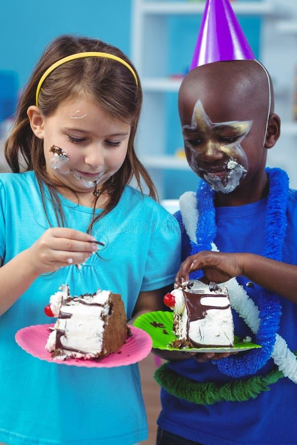 Bambini felici che mangiano torta di compleanno fotografia stock libera da diritti
