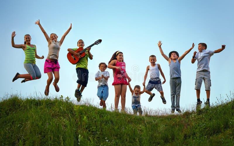 Bambini felici che saltano sul campo di estate fotografie stock