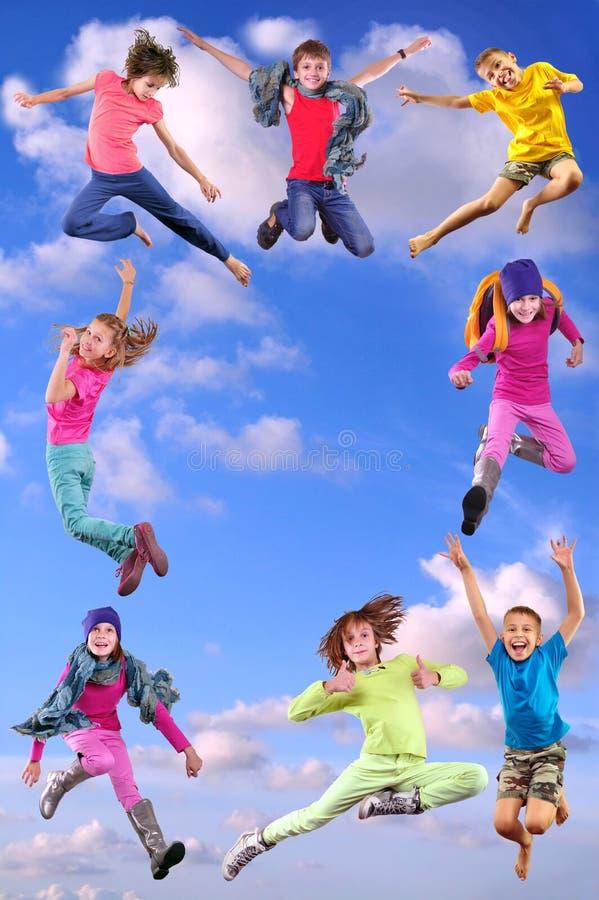 Bambini felici che si esercitano e che saltano nel cielo blu fotografia stock