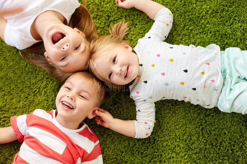 Bambini felici che si trovano sul pavimento o sul tappeto immagine stock