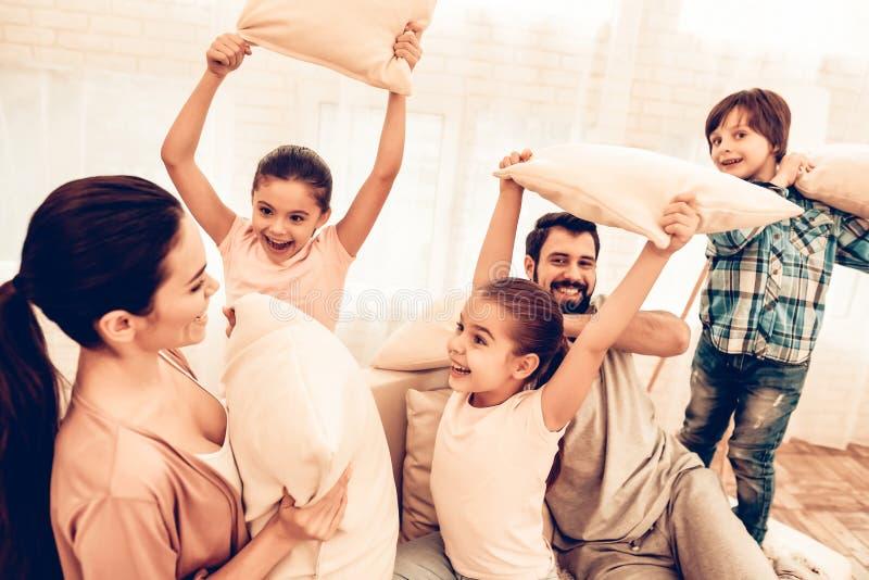 Bambini felici con i genitori che hanno lotta di cuscino immagini stock libere da diritti