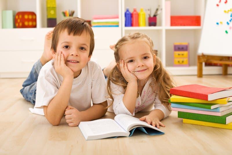 Bambini felici con i libri che pongono sul pavimento immagine stock libera da diritti