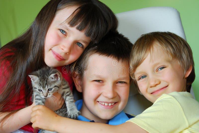 Bambini felici con il gattino immagini stock libere da diritti