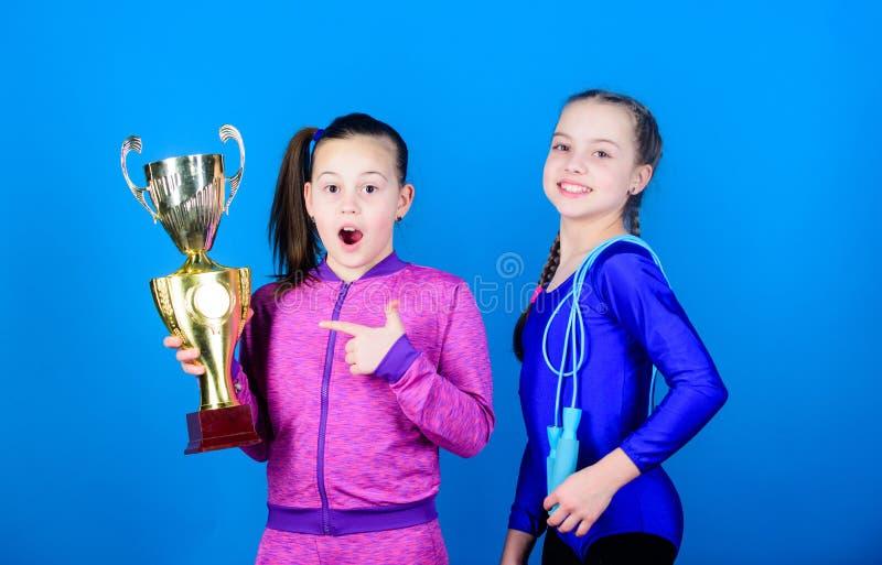 Bambini felici con la tazza di campione dell'oro Acrobatica e ginnastica Le bambine tengono la corda di salto vittoria delle raga immagini stock