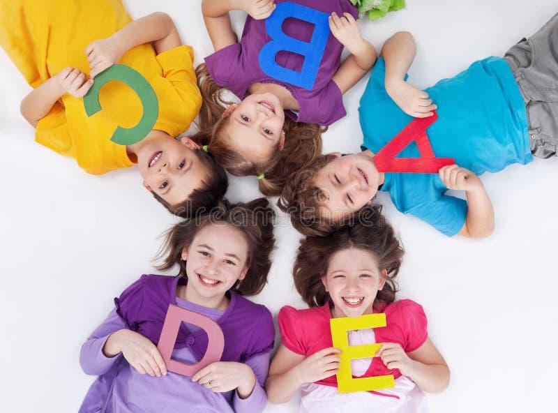 Bambini felici del banco con le lettere variopinte di alfabeto fotografie stock