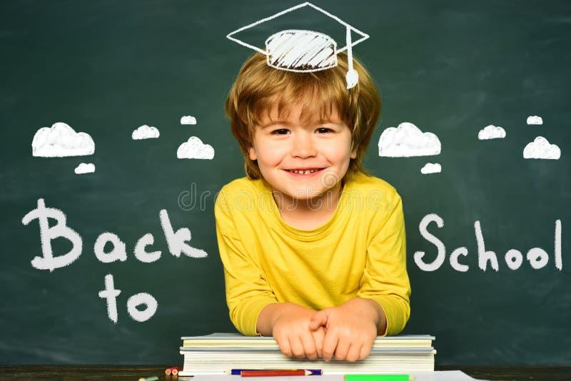Bambini felici del banco Concetto del banco Aula Ragazzino divertente che indica su sulla lavagna Bambini della scuola contro ver immagine stock libera da diritti