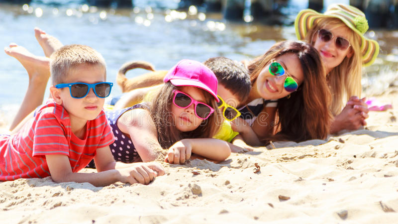 Bambini felici delle donne della famiglia che prendono il sole sulla spiaggia fotografie stock libere da diritti