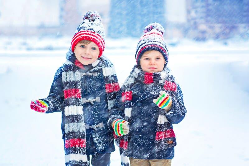 Bambini felici divertendosi con la neve nell'inverno fotografia stock libera da diritti