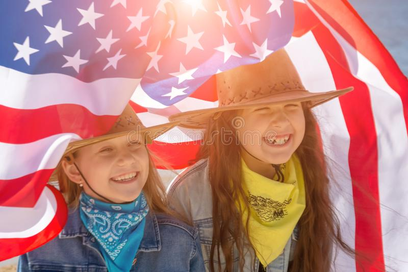 Bambini felici, due ragazze sveglie con la bandiera americana cowboy immagine stock