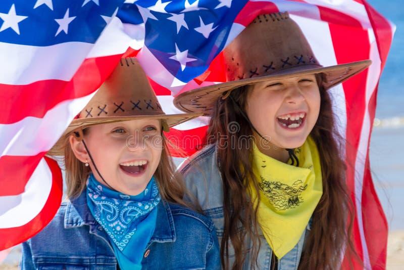 Bambini felici, due ragazze sveglie con la bandiera americana immagini stock