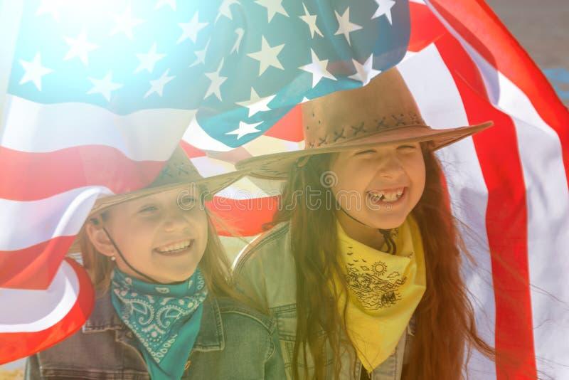 Bambini felici, due ragazze sveglie con la bandiera americana fotografie stock libere da diritti
