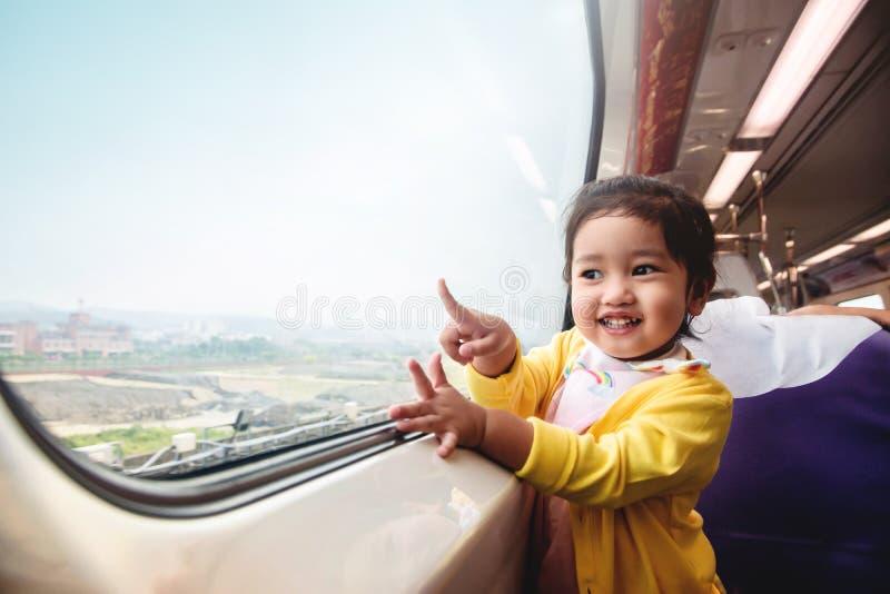 Bambini felici ed emozionanti che viaggiano in treno Una ragazza di due anni immagini stock