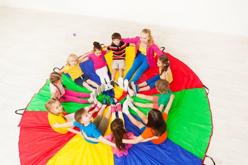 Bambini felici ed insegnante che si siedono sul paracadute fotografia stock