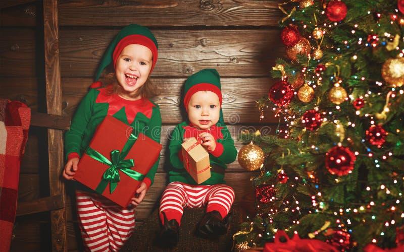 Bambini felici fratello ed elfo della sorella, assistente di Santa con Chri fotografie stock libere da diritti