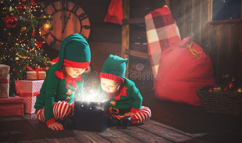 Bambini felici fratello ed elfo della sorella, assistente di Santa con Chri immagine stock