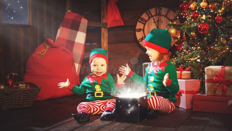Bambini felici fratello ed elfo della sorella, assistente di Santa con Chri immagine stock libera da diritti
