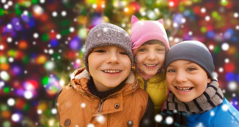 Bambini felici sopra le luci di natale e della neve fotografia stock