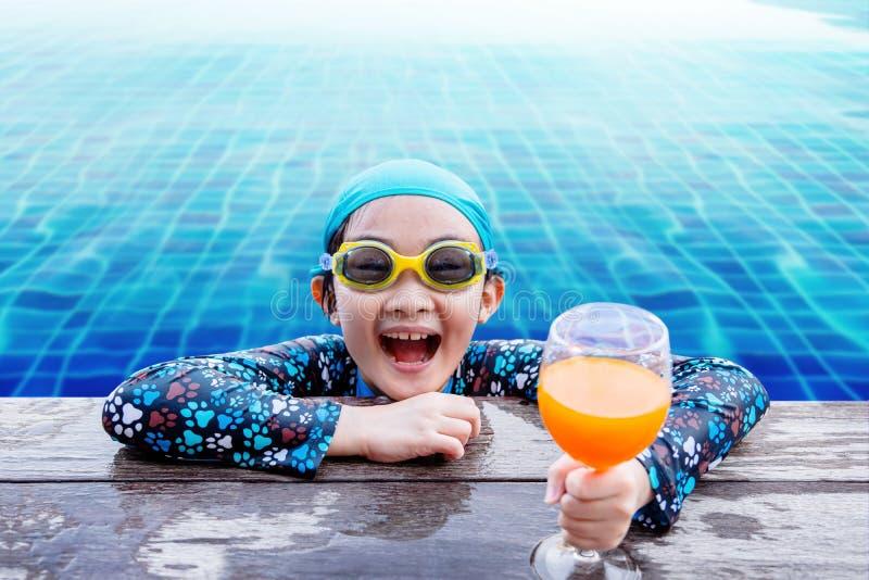 Bambini felici sul lato della piscina, ragazza che si rilassa con la somma immagini stock libere da diritti
