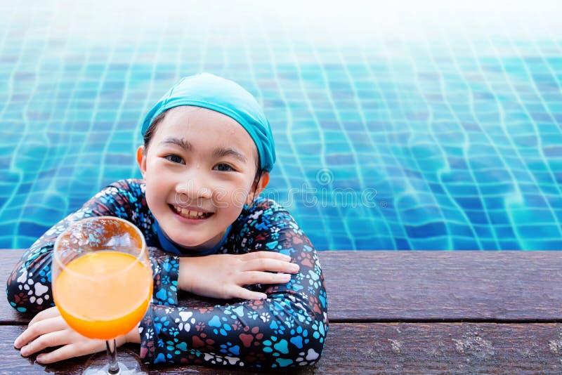 Bambini felici sul lato della piscina, ragazza che si rilassa con la somma fotografia stock libera da diritti
