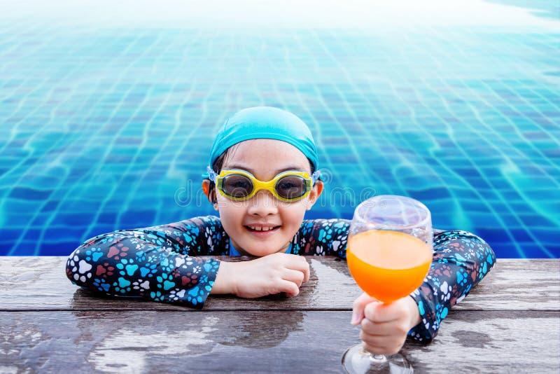 Bambini felici sul lato della piscina, ragazza che si rilassa con la somma immagine stock