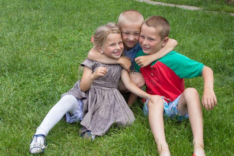 Bambini felici sull'erba, bambini che si abbracciano ridente mentre sedendosi sull'erba immagine stock libera da diritti