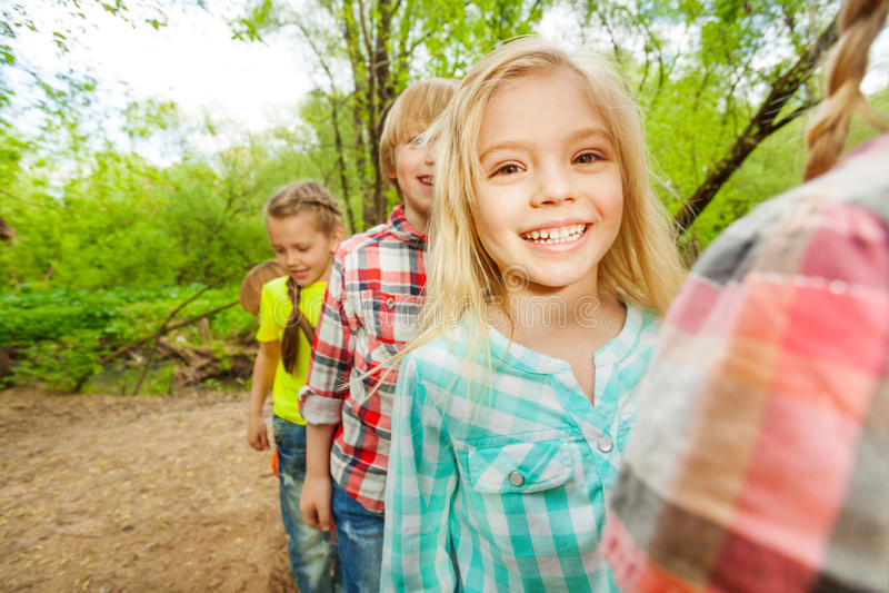 Bambini felici svegli che camminano insieme nella foresta immagine stock libera da diritti