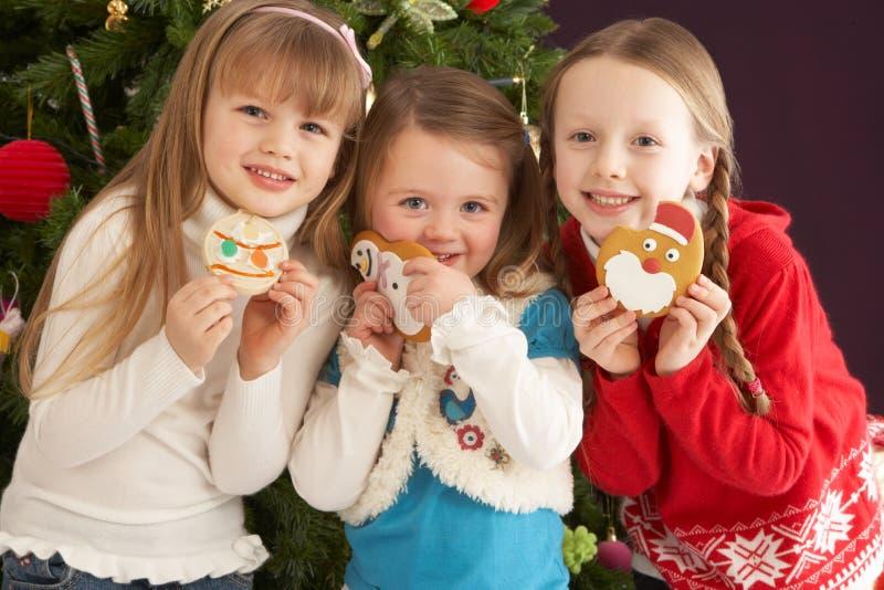Bambini in giovane età con i presente davanti all'albero fotografie stock libere da diritti