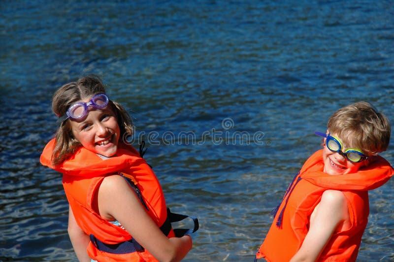 Bambini in giubbotti di salvataggio dal mare fotografia stock libera da diritti