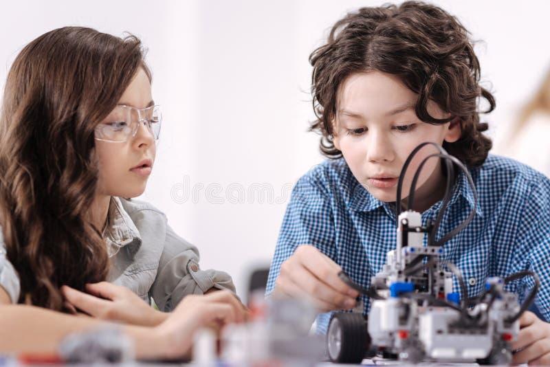 Bambini ingegnosi che creano robot alla scuola fotografia stock