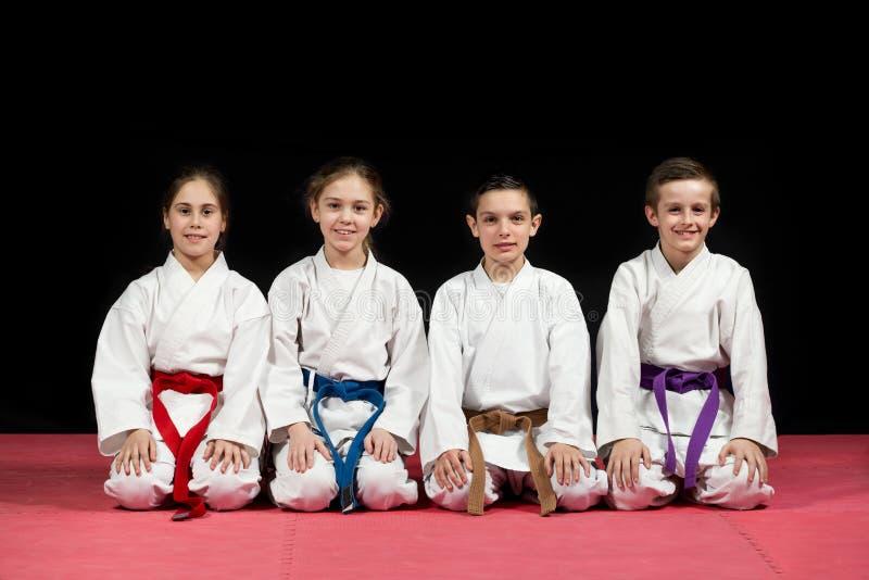 Bambini in kimono che si siede sul tatami sul seminario di arti marziali Fuoco selettivo fotografia stock