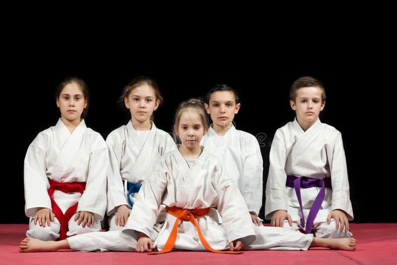 Bambini in kimono che si siede sul tatami sul seminario di arti marziali Fuoco selettivo immagine stock