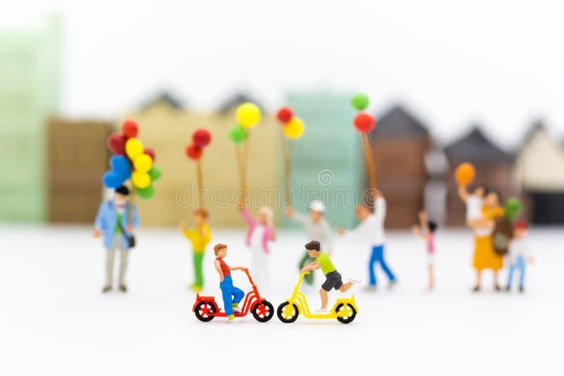 Bambini miniatura: Ragazzi che ciclano divertimento del gioco nel campo da giuoco Uso di immagine per il giorno del ` s dei bambi fotografia stock libera da diritti