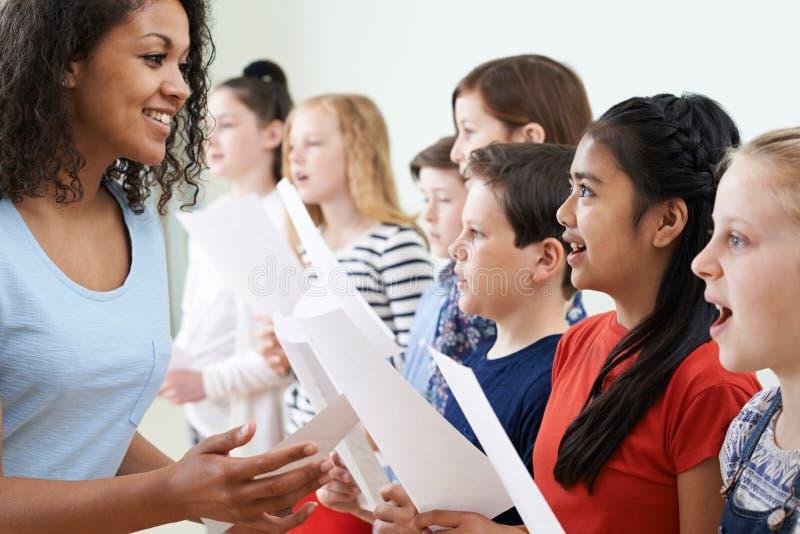 Bambini nel coro di scuola che è incoraggiato dall'insegnante immagine stock
