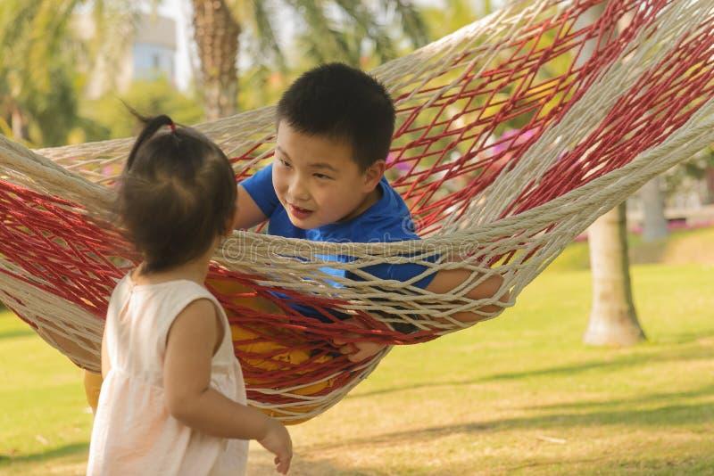 Bambini nella vacanza sull'amaca con il fondo del cocco fotografia stock libera da diritti