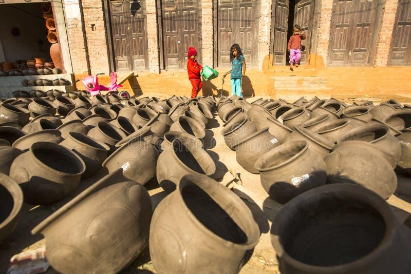 Bambini nepalesi nella sua officina delle terraglie immagini stock libere da diritti