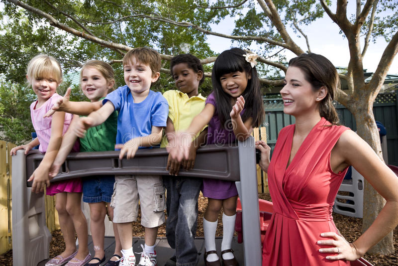 Bambini prescolari sul campo da giuoco con l'insegnante fotografie stock libere da diritti