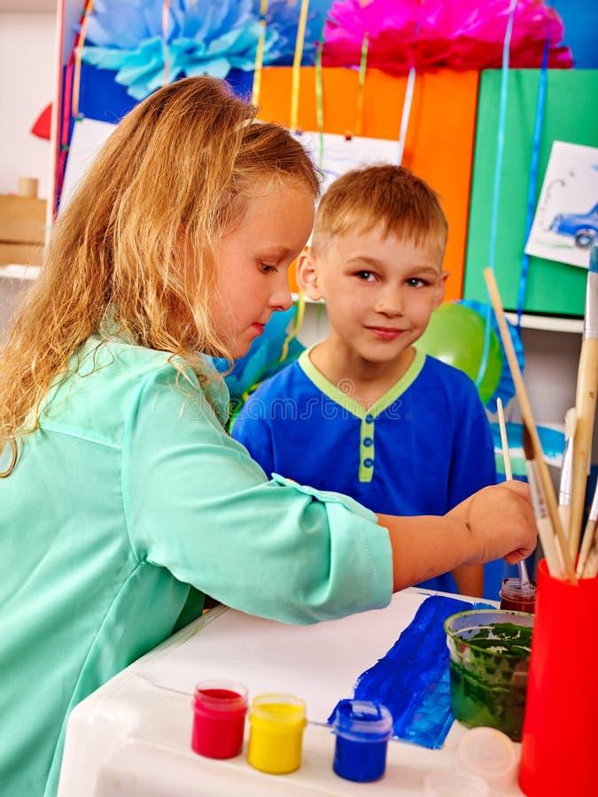 Bambini ragazza e ragazzo con la pittura della spazzola a scuola primaria fotografia stock libera da diritti