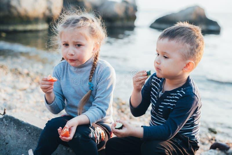 Bambini, ragazza e ragazzo mangianti pomodoro e cetriolo sul fondo del mare fotografie stock libere da diritti