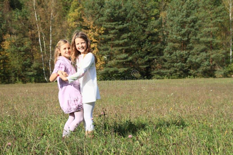 Bambini - ragazze che ballano sul prato immagine stock libera da diritti