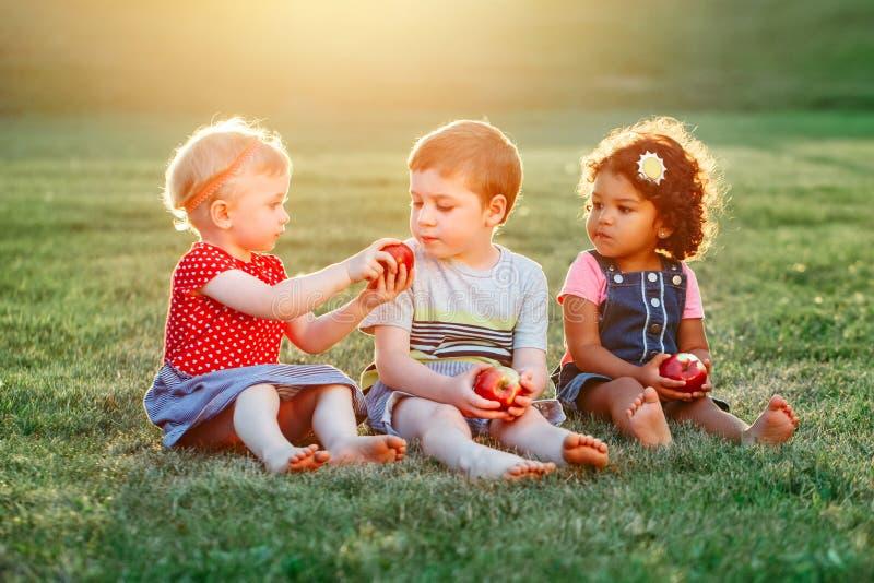 Bambini ragazzo e ragazze che si siedono insieme divisione e cibo dell'alimento della mela immagini stock libere da diritti