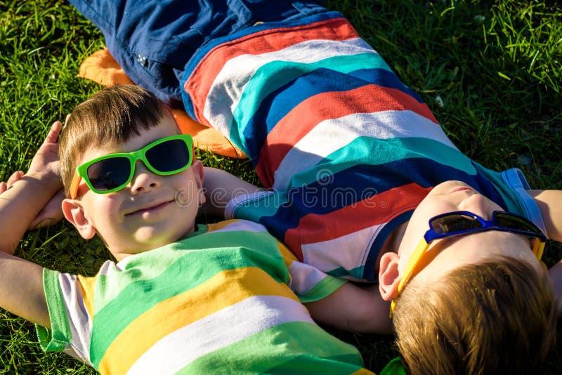Bambini sorridenti allegri felici, mettendo su un'erba, durare cantato immagine stock libera da diritti