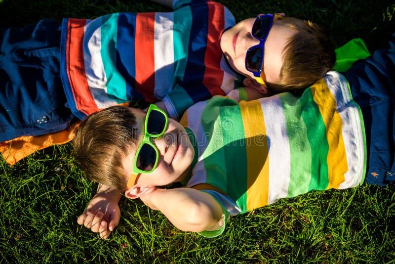 Bambini sorridenti allegri felici, mettendo su un'erba, durare cantato fotografia stock libera da diritti