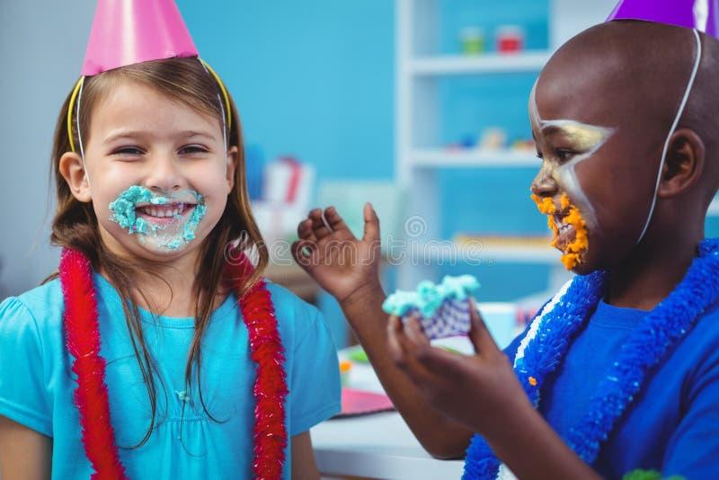 Bambini sorridenti con glassa sui loro fronti immagini stock
