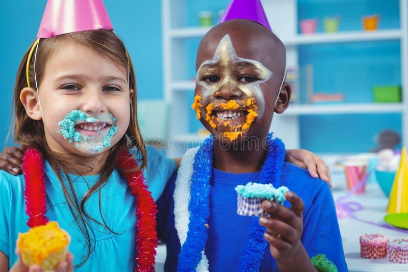 Bambini sorridenti con glassa sui loro fronti fotografia stock libera da diritti