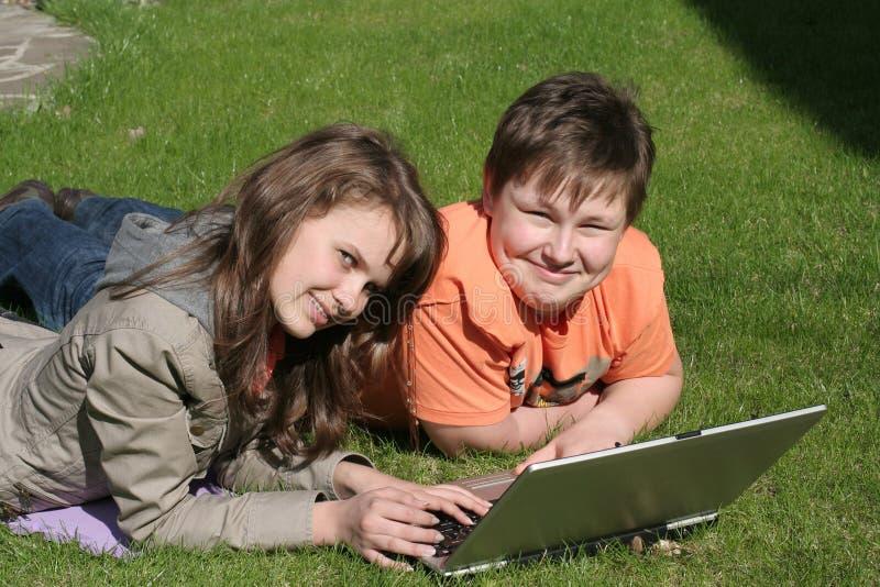 Bambini sorridenti con un computer portatile fotografia stock