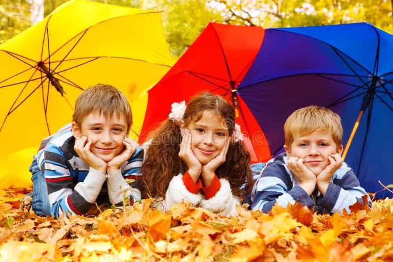 Bambini sotto gli ombrelli fotografia stock libera da diritti