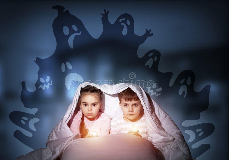 Bambini spaventati in pigiami con le torce elettriche immagini stock libere da diritti