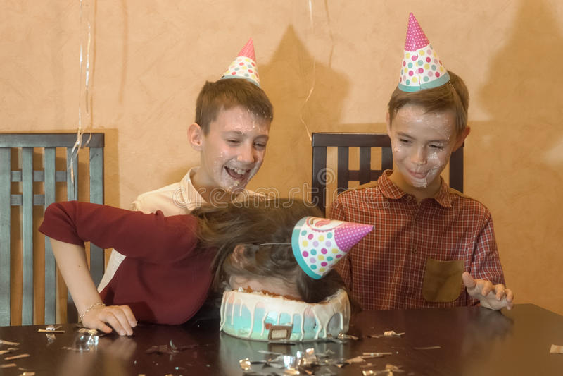 Bambini spensierati ad una festa di compleanno fronte dunked bambina nella torta di compleanno fotografia stock